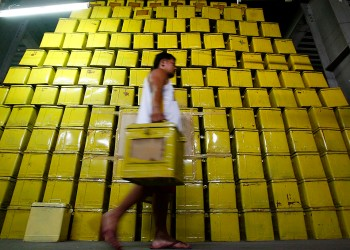 A worker carrying a ballot box walks past a pile of ballot boxes stored in a warehouse in Manila July 1, 2009. The Philippine government has given partners of a joint venture that won a $150 million bid to automate next year's elections until Friday to patch up their differences, the elections commission chief said on Tuesday. Jose Melo, chairman of the Commission on Elections, has said the automation plan was likely to be scrapped because of disagreements between Barbados-based Smartmatic Corp and local firm Total Information Management. REUTERS/Romeo Ranoco (PHILIPPINES POLITICS ELECTIONS IMAGES OF THE DAY)